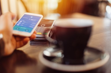 Male in cafe paying contactless with smartphone